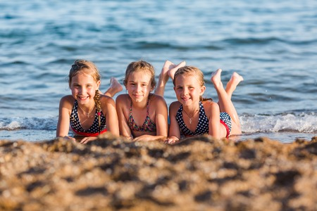 Happy kids on the beach having fun. Summer holiday concept Reklamní fotografie