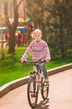 Happy little girl riding a bike in the park