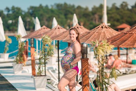 Beautiful pregnant woman relaxing in swimming-suit at the beach. Enjoying pregnancy concept.