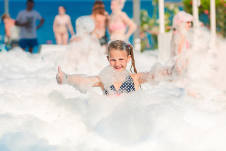 Foam Party on the beach. Cute little girl having fun and dancing.