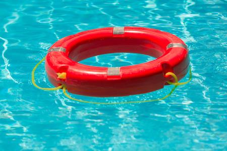 Life-saving orange buoy floating at the pool Reklamní fotografie