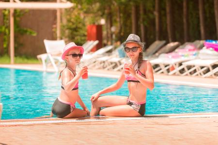 Happy girls at the pool having great time enjoying drinks