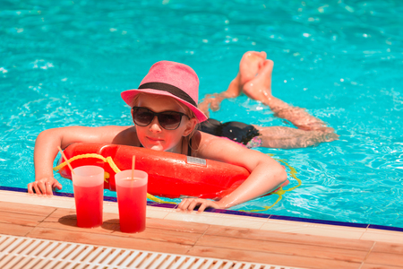 Happy girl at the pool having great time enjoying drink Reklamní fotografie