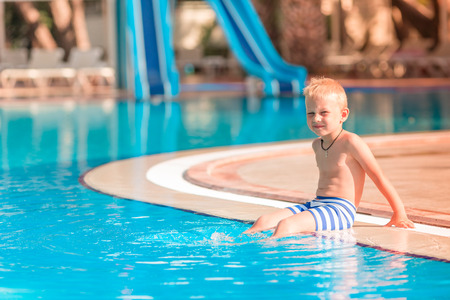Cute little boy sitting at the pool edge Reklamní fotografie