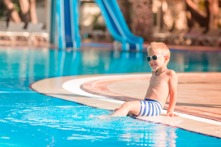 Cute little boy in sunglasses sitting at the pool edge