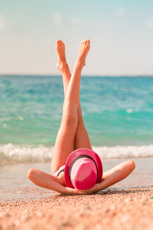 Back view of a young beautiful girl in a hat lying on the beach with her legs up