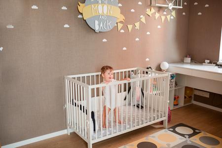 Netter kleiner Junge, der aus seinem Bett in seinem Zimmer schaut