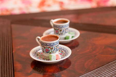 Two traditional porcelain turkish coffee cups with turkish delight on a table Reklamní fotografie
