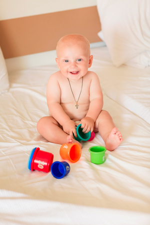 Cute little baby boy playing with stacking cups in the room