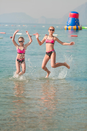 Happy young girls at the seaside sunbathing, having fun Stock Photo