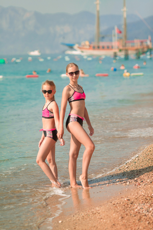 Happy young girls at the seaside sunbathing, having fun Reklamní fotografie