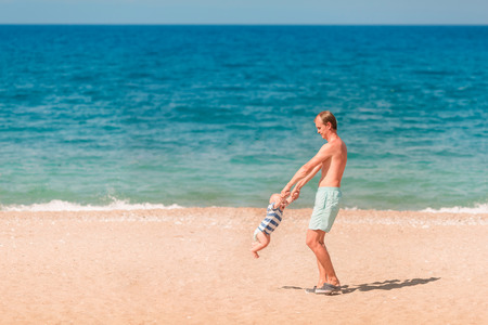Young happy father playing with his baby at the beach. Baby turning around, whirling Reklamní fotografie