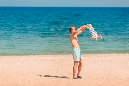 Young happy father playing with his baby at the beach. Baby turning around, whirling Archivio Fotografico