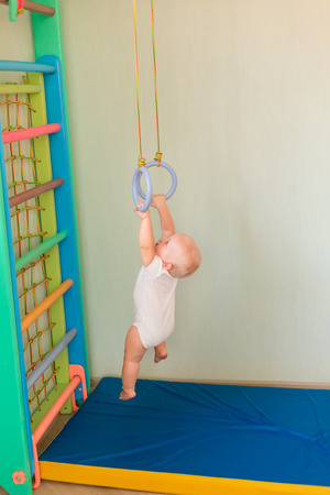 Cute baby boy hanging on rings on home wall gym. Baby early sportive development concept Reklamní fotografie