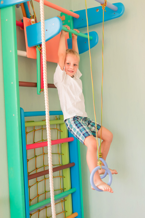 Happy little boy hanging on rings on home wall gym. Childs sportive development concept Reklamní fotografie