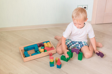 Cute little boy playing with colored wooden blocks in the room. Early development concept