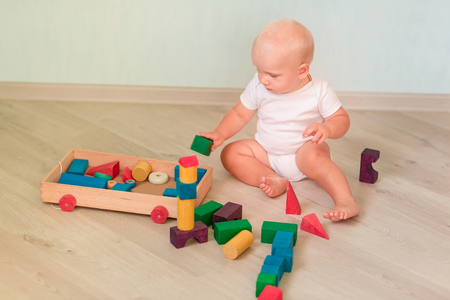 Cute little baby playing with colored wooden blocks in the room. Early development concept Reklamní fotografie