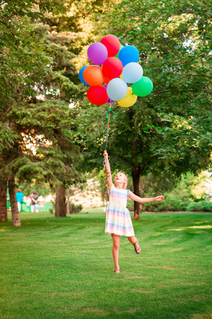Happy little girl playing with large bunch of helium filled colorful balloons in the park