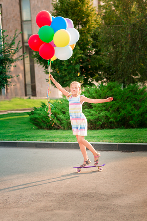 Happy little girl skating on a scateboard with large bunch of helium filled colorful balloons in the park