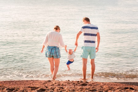 Happy family with baby at the seaside on the beach