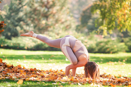 Beautiful young woman practicing yoga in the park outdoors