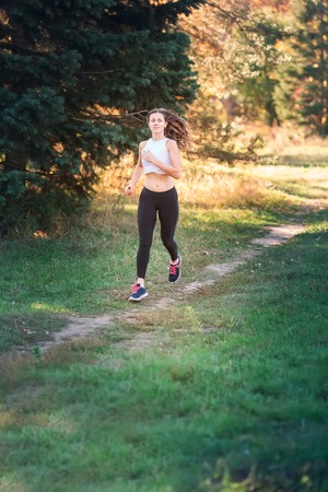 Beautiful young sportive woman jogging in the park in sunset light Reklamní fotografie