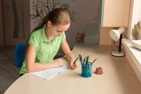 Cute little girl left-handed writing her homework at the table