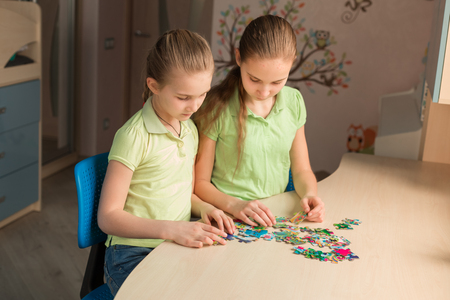 Two little girls solving puzzle together sitting at the table Reklamní fotografie