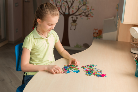 Cute little girl solving puzzle together sitting at the table
