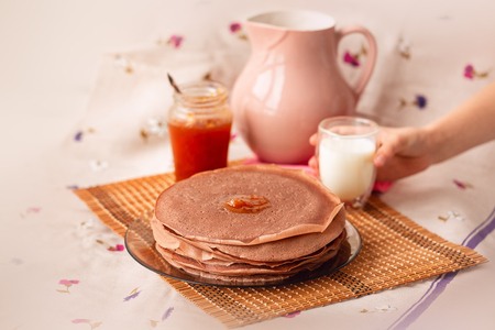 Many Russian-style thin pancakes with crispy crust served with cream and milk. Maslenitsa. Pancakes for breakfast and carnival