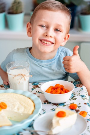 Beautiful little boy eating breakfast and drinking milk in kitchen at home
