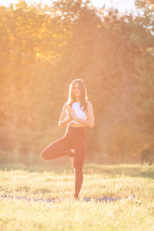 Beautiful young woman practicing yoga at sunset in the park outdoors