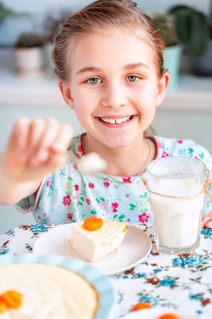 Beautiful little girl eating breakfast and drinking milk in kitchen at home Reklamní fotografie