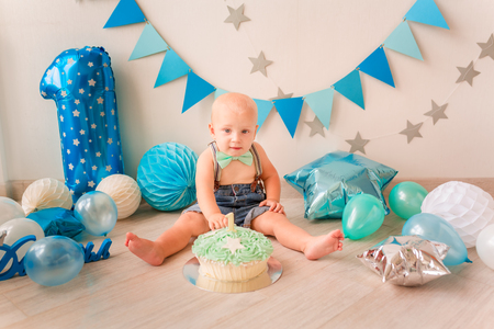 Adorable baby boy celebrating his first birthday. Smash cake party