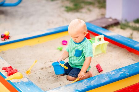 Cute baby boy playing with toys in the sandbox outdoor