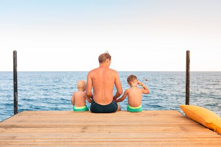 Father and sons swinging their legs from the wooden pier looking at the sea