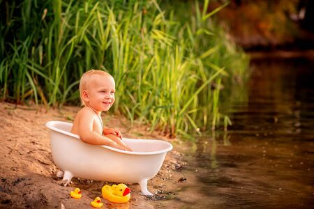 Cute baby boy playing with toy ducks in bathtub on the river bank Stock Photo