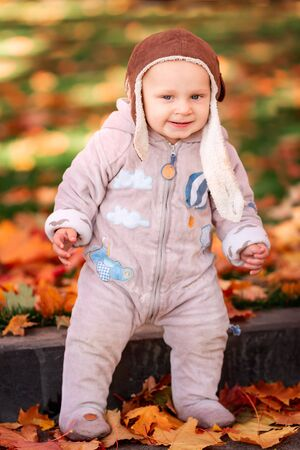 Cute little baby playing in autumn leaves. First autumn