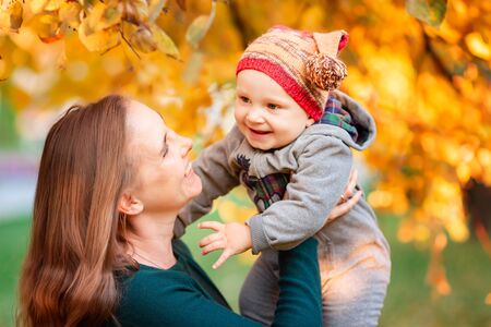 Happy mother and baby in autumn leaves outdoors