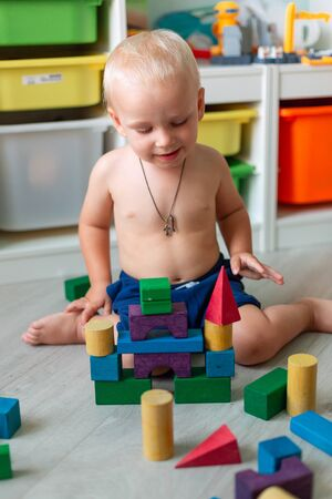 Cute baby boy playing with building blocks in kids room