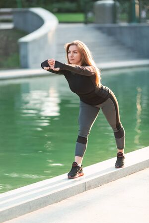 Fitness woman stretching outdoor in urban environment in the park on sunrise