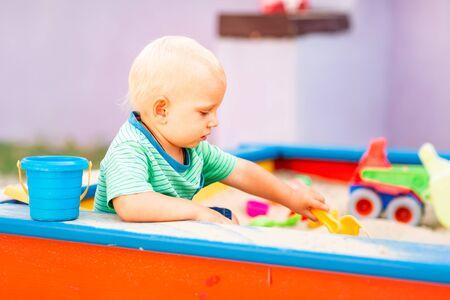 Mignon petit garçon jouant avec des jouets dans le bac à sable en plein air Banque d'images