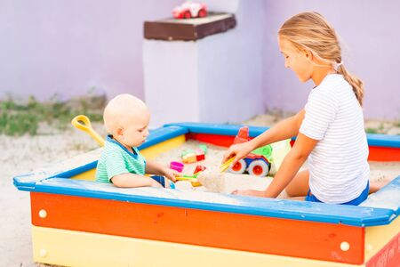 Cute baby boy playing with his sister with toys in the sandbox outdoor Stock Photo