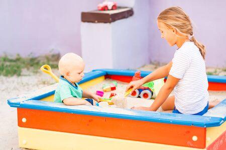 Süßes Baby spielt mit seiner Schwester mit Spielzeug im Sandkasten im Freien Standard-Bild