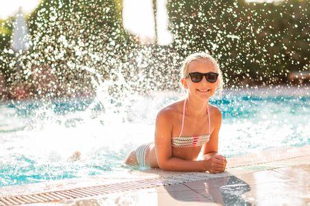 Happy beautiful girl having fun at the pool at the resort