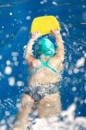 Cute little girl training in a swimming pool. Swimming sport for kids concept Banco de Imagens