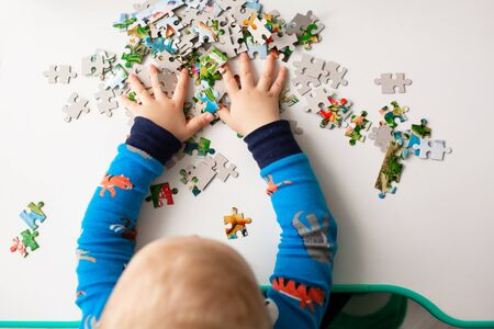 Baby boy solving jigsaw puzzle on the desk, focusing on the hands