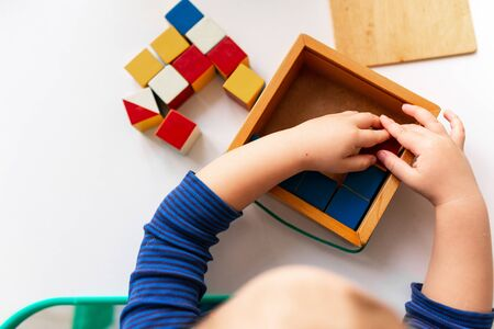 Baby playing with wooden blocks creating a pattern, focusing on hands. Nikitin unicube game