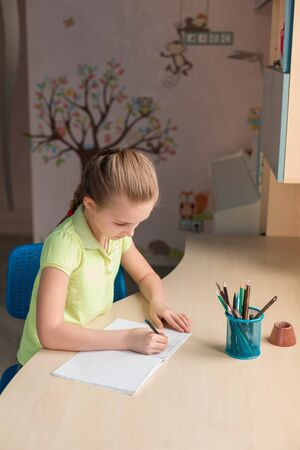 Cute little girl writing her homework at the table in her room