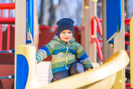 Happy little baby boy playing on the playground outdoor